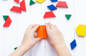 A child plays with colored blocks constructs a model on a light wooden background