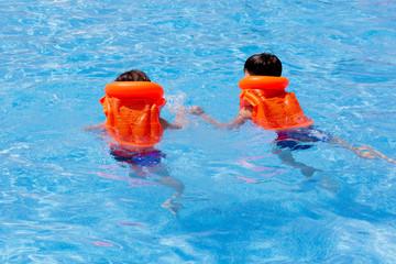 Children, 2 boys in rescue zhelekah swim in the water. Pool