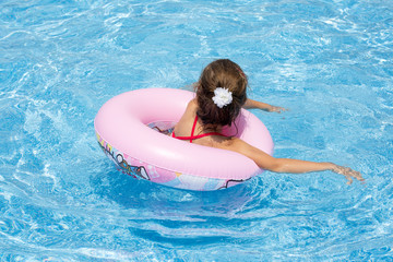 The girl swims in a pink inflatable circle in the pool.