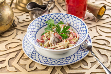 Vegetable salad with apple and beef and glass of berry juice on oriental table