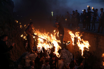 Iraqi Kurdish people carry fire torches, as they celebrate Nowruz Day, a festival marking the first day of spring and the new year, in the town of Akra