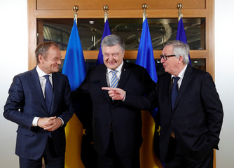Ukraine's President Petro Poroshenko is welcomed by President of the European Council Donald Tusk and European Commission President Jean-Claude Juncker at the Europa building in Brussels