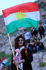 A Kurdish Iraqi woman holds the Kurdish flag, as she celebrates Nowruz Day, a festival marking the first day of spring and the new year, in the town of Akra near Duhok