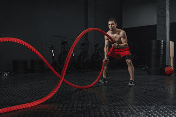 Young athlete doing battle ropes exercise at the crossfit gym