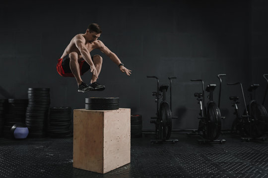 Young crossfit athlete doing box jump exercise at the gym