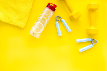 Fitness set with bars, towel, bottle of water and wrist builder on yellow background top view mock up