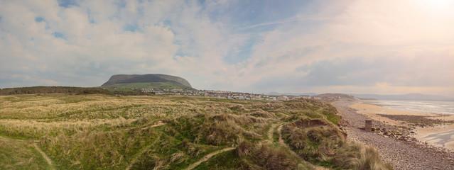 Panorama image of Knocknarea hill, Queen Maeve grave, Silver Strand, county Sligo Ireland, Cloudy sky, warm sun halo.