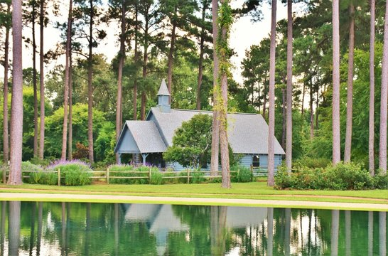 Gray church amid pine trees with reflection in infinity pond