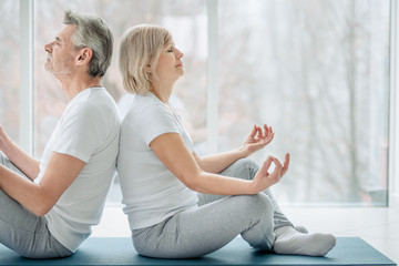 Meditation together.Cropped picture of senior couple doing yoga together in the white gym. Health and sport concept.