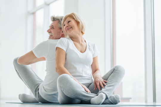 Sport and health concept.Senior couple sitting on the mat back to back laughing and talking. Leisure time in the training.