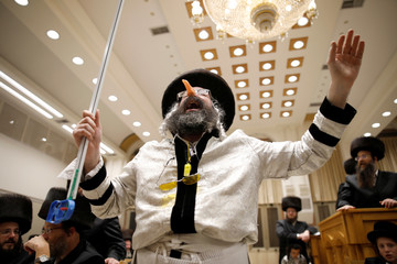 An Ultra-Orthodox Jewish man dressed in a costume takes part in the reading from the Book of Esther, a ceremony performed on the Jewish holiday of Purim, in a synagogue in Ashdod