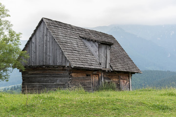 Old wooden barn in field with mountains in background