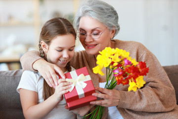 mother's and grandmothers day!   family granddaughter congratulates her grandmother on holiday and gives flowers and gifts.