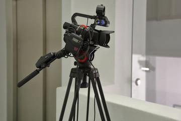 Modern professional HD video camera on a black tripod