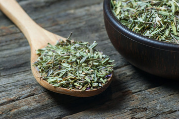 Heap of dry thyme in wooden spoon and in bowl on wooden background. Dried spice zahter thyme and oil concept