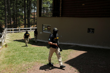Agents of the Technical Criminal Investigation Agency (ATIC) keep watch at a property belonging to former first lady Rosa Elena Bonilla, currently detained on embezzlement charges, in Tegucigalpa