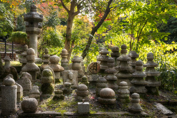 Kyoto, Japan - November 2, 2018: Graveyard stones with sunset light from behind at the famous Kiyomizu-dera Buddhist Temple, in Gion District, Kyoto, Japan.