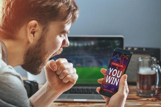 Man celebrating victory after making bets at bookmaker website