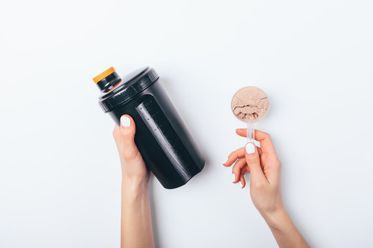 Female's hands holding scoop of chocolate protein powder