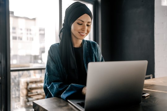 Young Muslim woman working remotely on a laptop sitting in the office