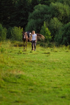 Young blond woman with long hair jockey rider jumping on a bay horse on a background of field and forest