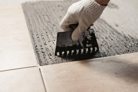 The hands of the tiler are laying the ceramic tile on the floor. Close up macro shot. Home renovation and building new house concept