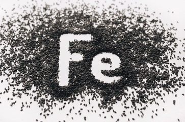 Fototapeta Chemical element - Fe. The word Ferrum in abbreviated form is written in black sesame seeds on a white background. The concept of healthy eating, iron, vegetarianism and metabolism. Close up. obraz