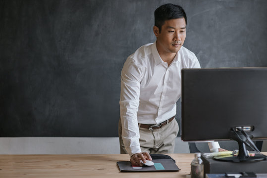 Asian businessman standing at his desk working on a computer