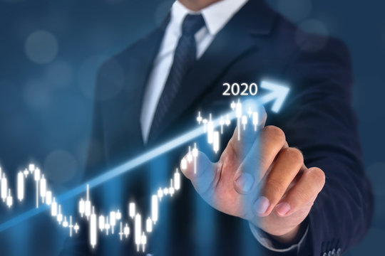 year 2020 business man point hand on the top of arrow graph with high rate of growth. The success and growing growth graph in the company or industrial after investment in 2020 and preparing for 2021