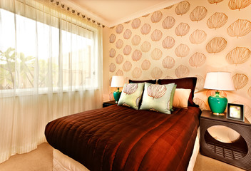 Modern bedroom interior decoration with a fancy table both sides from bed holding table lamps.