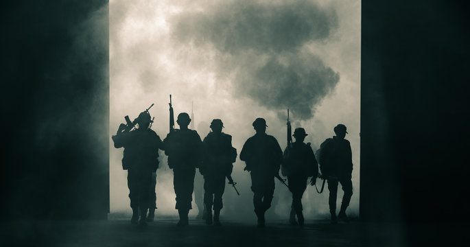 silhouette thai soldiers special forces team full uniform walking action through smoke and holding gun on hand