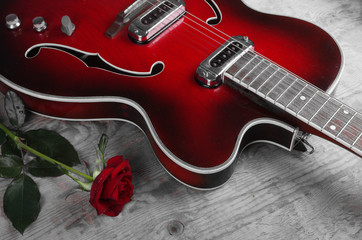 Electric guitar and red rose on a wooden table
