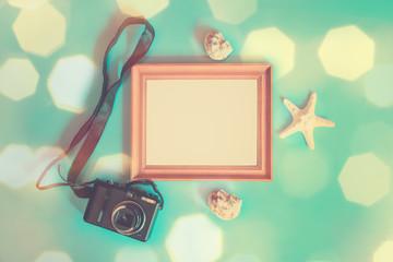 Summer beach holiday concept. Photo frame, photo camera, starfish and seashells on blue background.