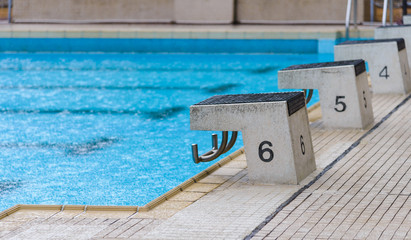 empty diving block stands with numbers in outdoor swimming pool on rainy day