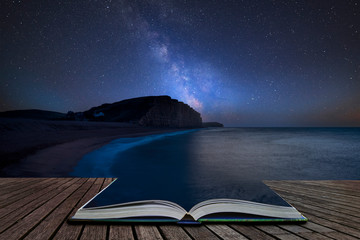 Vibrant Milky Way composite image over landscape of long exposure of West Bay in Dorset  coming out of pages in magical story book