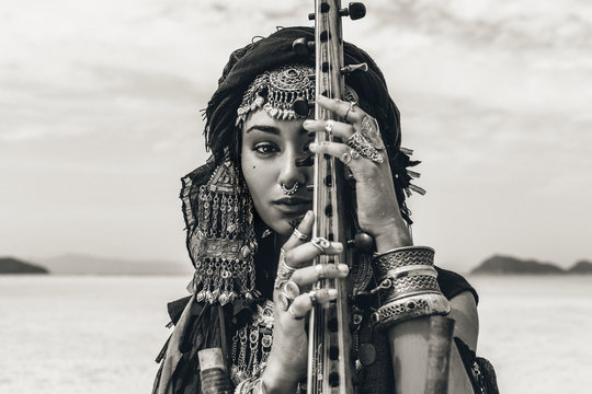 Beautiful young stylish tribal woman in oriental costume playing sitar outdoors. Close up