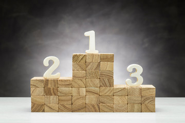 Concept of competition. Wooden podium on grey background with numbers.