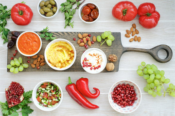 Middle Eastern appetizers. Hummus, labneh, muhammar dip sauce in bowls. Olives, sun-dried tomatoes, vegetables, fruits, nuts and herbs on white wooden background