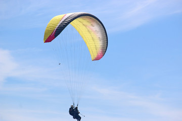 Fototapete - Tandem paraglider flying yellow wing