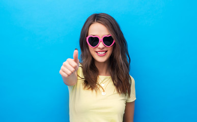 summer, valentine's day and people concept - smiling young woman or teenage girl in yellow t-shirt and heart-shaped sunglasses showing thumbs up over bright blue background