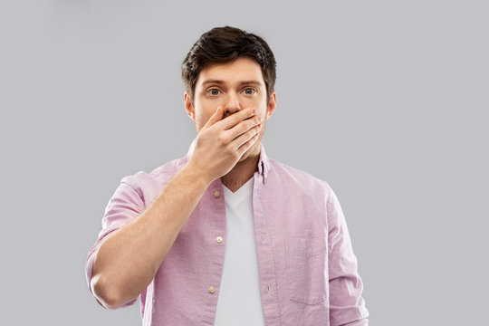 emotion, expression and people concept - shocked and speechless young man covering his mouth by hand over grey background