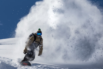 male snowboarder curved and brakes spraying loose deep snow on the freeride slope Wall mural