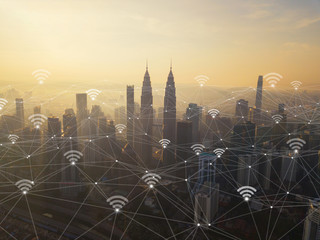 Digital network connection lines and wifi icons with Kuala Lumpur Downtown, Malaysia. Financial district in smart city in technology concept. Skyscraper and high-rise buildings at sunset
