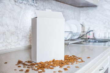 Generic box of cereals on the kitchen table. White package of ready breakfast in home background