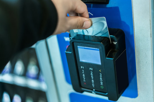 Hand using credit card on vending machine