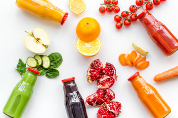 bottles with fresh carrot, tomato, apple, cucumber, lemon, pomegranate juices on white background top view copyspace