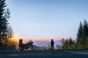 girl in full motorcycle equipment, stands on the side of the road over a cliff and looks into the...