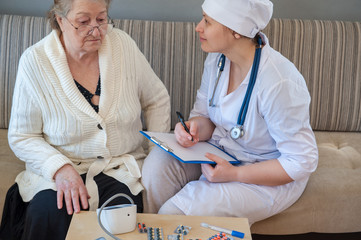 Pretty nurse in white coat helps sick retiree on social assistance program. Nurse carefully examines prescription of drugs, makes injections, measures blood pressure and cares.