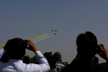 People take photos of Chinese J-10 fighter jets during rehearsal in Islamabad