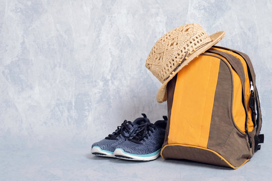 hiking backpack with footwear and straw hat on grey background, banner mockup with copy space for your text, concept of adventure, hiking, summer travel with carry on backpack